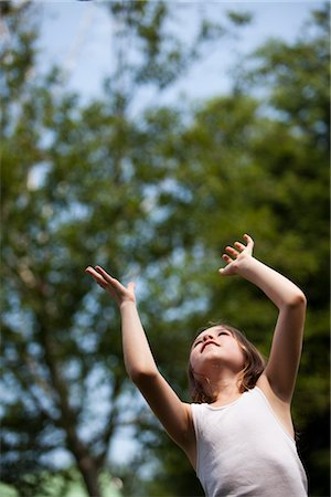 preteen girls stretching - Young Girl with Arms Raised Looking Up Stock Photo - Rights-Managed, Code: 822-05555019