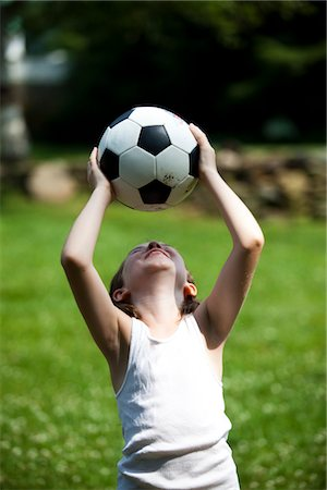 Smiling Young Girl Holding Football Above Head Stock Photo - Rights-Managed, Code: 822-05555020