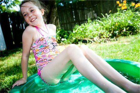 preteen girl swimsuit - Girl Leaning on the Edge of Paddling Pool Stock Photo - Rights-Managed, Code: 822-05555126