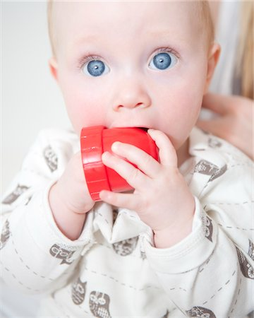 Wide Eyed Baby Biting Toy, Close-up view Stock Photo - Rights-Managed, Code: 822-05555154