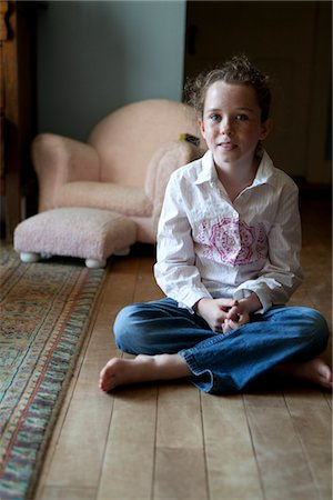 Girl Sitting Cross Legged on Wood Flooring Stock Photo - Rights-Managed, Code: 822-05555163