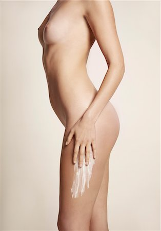 personal care - Side View of Nude Woman Applying Body Lotion on Thigh Stock Photo - Rights-Managed, Code: 822-05948420