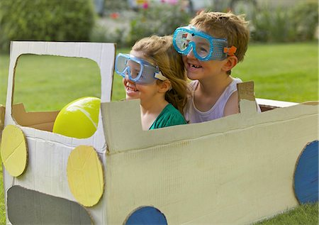 Boy and Girl Wearing Goggles Driving Cardboard Car Stock Photo - Rights-Managed, Code: 822-06302460