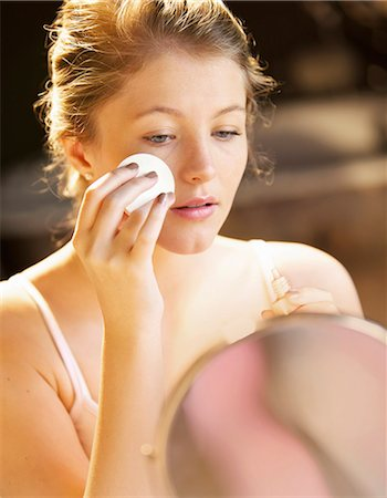 personal care - Young Woman Applying Makeup with Cotton Pad Stock Photo - Rights-Managed, Code: 822-06302470