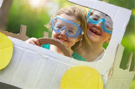 Boy and Girl Wearing Goggles Driving Cardboard Car Stock Photo - Rights-Managed, Code: 822-06302494