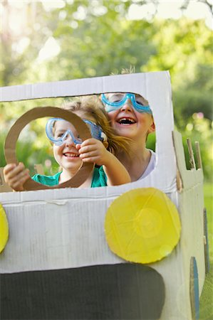 Boy and Girl Wearing Goggles Driving Cardboard Car Stock Photo - Rights-Managed, Code: 822-06302493