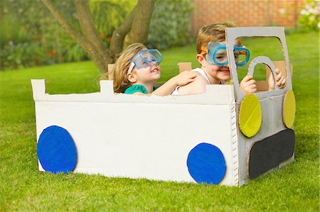 Boy and Girl Wearing Goggles Driving Cardboard Car Stock Photo - Rights-Managed, Code: 822-06302528