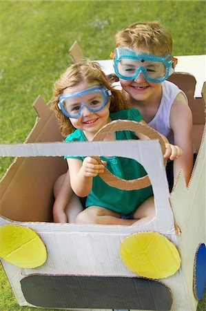 Boy and Girl Wearing Goggles Driving Cardboard Car Stock Photo - Rights-Managed, Code: 822-06302529
