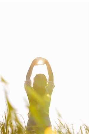 Back View of Woman Standing in a Field with Sun Shining through her Hands Stock Photo - Rights-Managed, Code: 822-06302556