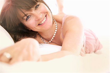 Smiling Woman Lying on Bed, Close-up View Stock Photo - Rights-Managed, Code: 822-06302569