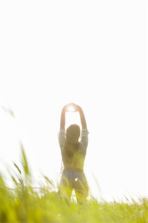 sun - Back View of Woman Standing in a Field with Sun Shining through her Hands Stock Photo - Rights-Managed, Code: 822-06302609