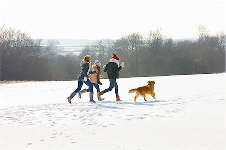 friendship - Teenage Girls and Dog Running in Snow Stock Photo - Rights-Managed, Code: 822-06302622