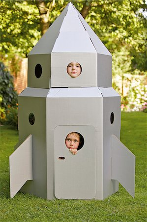 Two Boys Looking Out from Window of Cardboard Rocket Spacecraft Stock Photo - Rights-Managed, Code: 822-06302668
