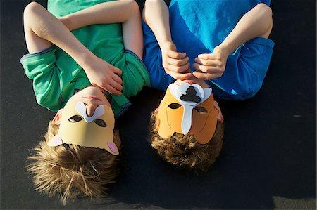 Two Boys Wearing Animal Masks lying on Back Stock Photo - Rights-Managed, Code: 822-06302702