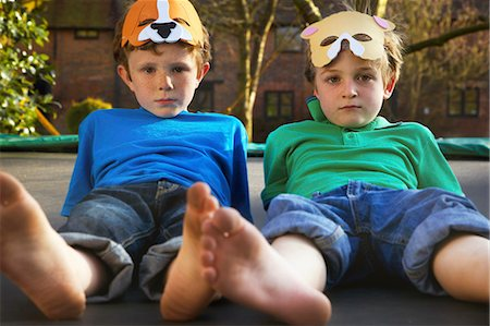 Two Boys Wearing Masks Lying on Trampoline Stock Photo - Rights-Managed, Code: 822-06302748