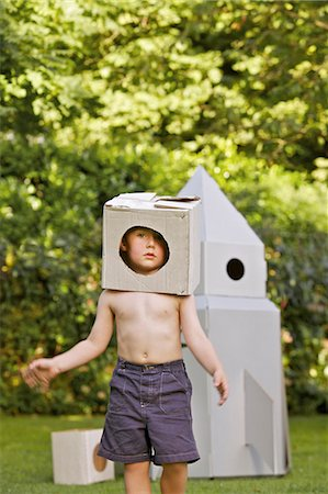 Boy Wearing Homemade Cardboard Helmet Playing in front of Rocket Spacecraft Stock Photo - Rights-Managed, Code: 822-06302753