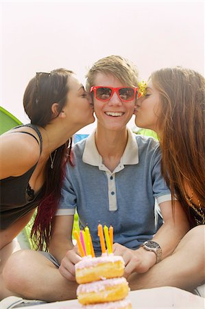 Two Teenage Girls Kissing Teen Boy in front of Birthday Cake Stock Photo - Rights-Managed, Code: 822-06702179