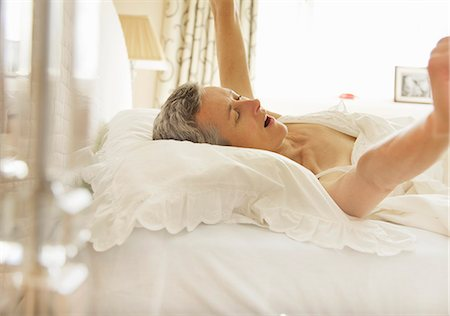 Woman in Bed Yawning and Stretching Arms Stock Photo - Rights-Managed, Code: 822-06702201