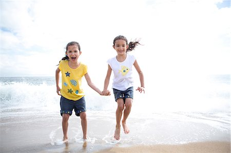families playing on the beach - Twin Girls Jumping Over Waves Stock Photo - Rights-Managed, Code: 822-06702212