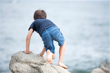 Boy Climbing Rock by Sea Stock Photo - Rights-Managed, Code: 822-06702307