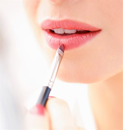 Woman Applying Lipstick with Makeup Brush, Close-up View Stock Photo - Rights-Managed, Code: 822-06702300