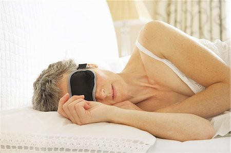 Woman In Bed Wearing Sleep Mask Stock Photo - Rights-Managed, Code: 822-06702362