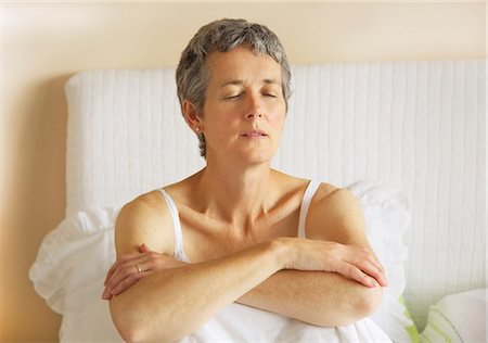 Woman Sitting in Bed with Arms Crossed Stock Photo - Rights-Managed, Code: 822-06702379