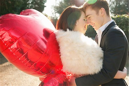 Young Couple Embracing Holding Heart Shaped Balloons Stock Photo - Rights-Managed, Code: 822-06702443