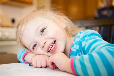 Smiling Girl Resting Head on Table Stock Photo - Rights-Managed, Code: 822-06702485