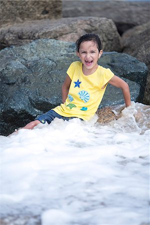 Girl Sitting on Rocks Playing in Sea Waves Stock Photo - Rights-Managed, Code: 822-06702504