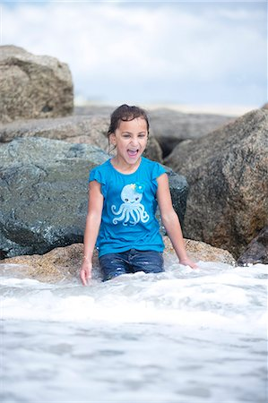 Girl Sitting on Rocks Playing in Sea Waves Stock Photo - Rights-Managed, Code: 822-06702505