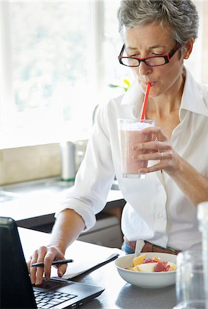 Woman Drinking Smoothie whilst Typing on Laptop Stock Photo - Rights-Managed, Code: 822-06702506