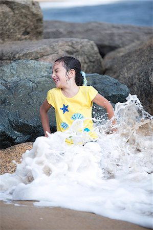 Girl Sitting on Rocks Playing in Sea Waves Stock Photo - Rights-Managed, Code: 822-06702528