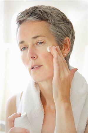 Woman Applying Moisturizing Cream on Face Stock Photo - Rights-Managed, Code: 822-06702545