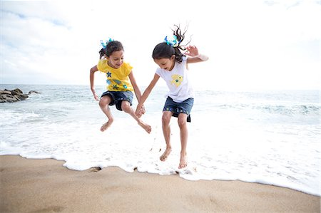 families playing on the beach - Twin Girls Jumping Over Waves Stock Photo - Rights-Managed, Code: 822-06702560