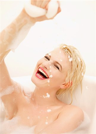 Smiling Young Woman Having a Bath Playing with Foam Stock Photo - Rights-Managed, Code: 822-07117323