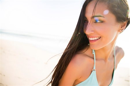 Smiling Young Woman Looking Over Shoulder Stock Photo - Rights-Managed, Code: 822-07117333