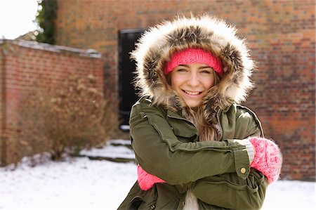 Smiling Teenage Girl Wearing Parka Hugging Herself Outdoors Stock Photo - Rights-Managed, Code: 822-07117402