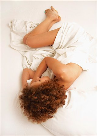Woman Wrapped in Sheet Curled Up in Bed Stock Photo - Rights-Managed, Code: 822-07117454