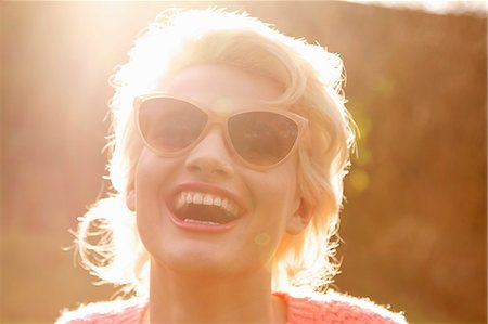 dark glasses - Smiling Young Woman Outdoors, Close-up View Stock Photo - Rights-Managed, Code: 822-07117482