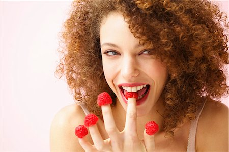 seductive - Smiling Young Woman Biting and Wearing Raspberries on Fingertips Stock Photo - Rights-Managed, Code: 822-07117531