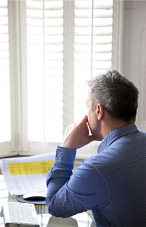 Man Sitting at Desk Looking Over Document Stock Photo - Rights-Managed, Code: 822-07117546