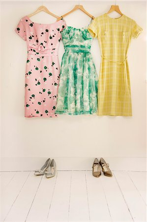 Dresses Hanging against White Wall with Shoes Stock Photo - Rights-Managed, Code: 822-07117556