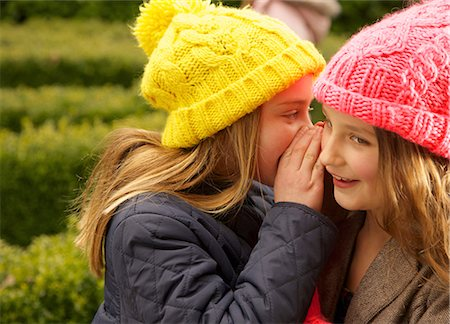 Young Girl Whispering in Friend's Ear Stock Photo - Rights-Managed, Code: 822-07117550