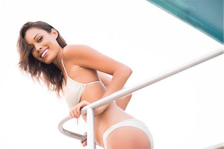 Smiling Woman Wearing Bikini Leaning on Railing Stock Photo - Rights-Managed, Code: 822-07355517