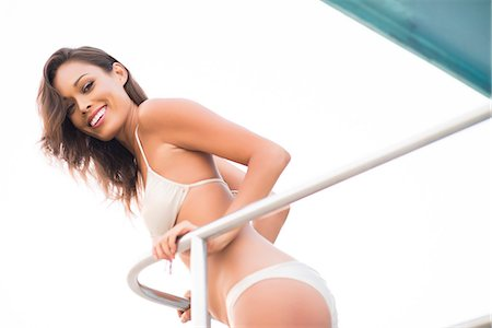 Smiling Woman Wearing Bikini Leaning on Railing Stock Photo - Rights-Managed, Code: 822-07355517