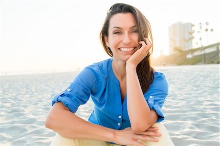 Smiling Woman Sitting on Sand Stock Photo - Rights-Managed, Code: 822-07355557