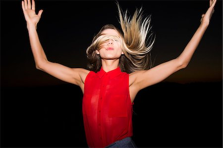 Young Woman with Arms Raised Flipping Hair Stock Photo - Rights-Managed, Code: 822-07355590