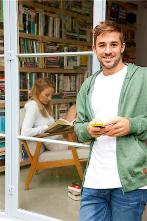 Smiling Man Standing in Doorway Holding Smartphone Stock Photo - Rights-Managed, Code: 822-07562544