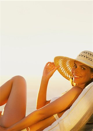 Smiling Woman Wearing Straw Hat Reclining on Sun Lounger Stock Photo - Rights-Managed, Code: 822-07562571